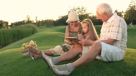 бабушка : Girl with grandparents, photo album. People looking at photos outdoors. Pages of the past. Стоковые видеозаписи