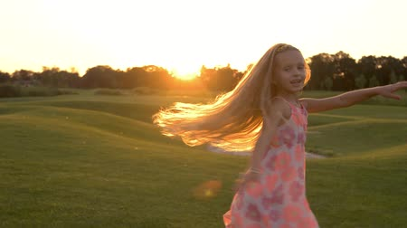 teen age : Cute little girl dancing on grass. Adorable child is spinning outdoors. Childhood and freedom.