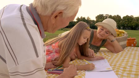 význam : Girl drawing with pencil outdoors. Grandmother giving advice to her granddaughter how to draw, nature background. Importance of help and support for kids.