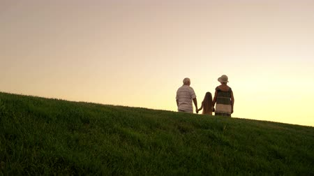 urlop : People walking on evening sky background. Girl and grandparents holding hands and walking beyond horizon. Leave the past behind.