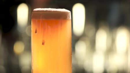 overfill : Glass of beer rotating and overflowing. Close up mug of light beer with foam dripping.