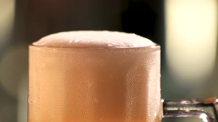 suds : Beer foam and bubbles. Foam bubbles in rotating glass of beer, close up.