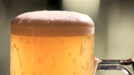 churn : Full mug cold amber beer. Glass of golden light beer bubbles, froth dripping.
