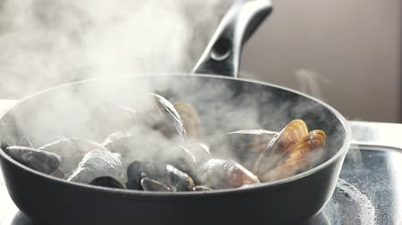 seafood recipe : Close up mussels cooking in a hot pan. Steaming pan with mussels, slow-motion.