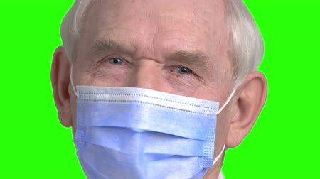 splatnost : Close up old doctor face with mask. Portrait of senior surgery doctor, green hroma background.