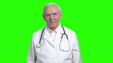 splatnost : Portrait of old frown doctor sighing. Doctor is preparing to tell bad news and breathing hard. Hromakey background. Dostupné videozáznamy