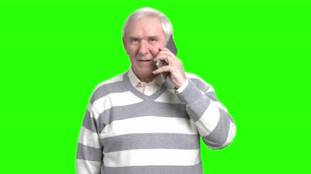 maturità : Senior man arguing on phone. Angry senior man speaking on the phone with somebody in green hromakey background. Filmati Stock