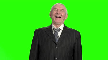 harts : Old businessman heartily laughing, slow-motion. Senior businessman laughing against green hromakey background. Stockvideo