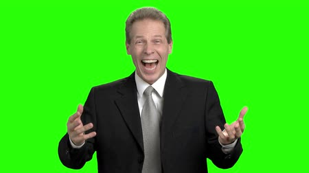 keying : Mature businessman suddenly cheering up. Middle aged man with business suit suddenly cheering up and laughing against green hromakey background. Stock Footage