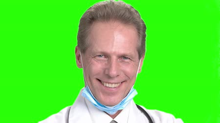 hanedan arması : Mature smiling doctors face. Cheerful doctor in green hroma background.
