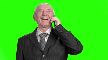 energized : Senior businessman talking on phone and laughing. Granddad in suit talking on phone and laughing out loud. Stock Footage