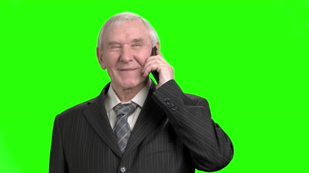 energized : Cheerful old politician talking on phone. Happy senior politition talking on phone with his family and laughing, green hroma background.
