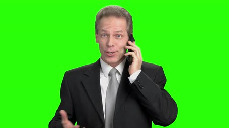 urge : Excited energized mature man talking on phone. Thrilled man in suit talking on phone, green background. Stock Footage
