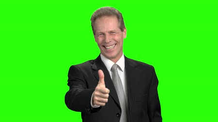 energized : Mature clerk in suit shows thumb up. Cheerful man smiling with teeth and shows like, green hromakey background. Stock Footage