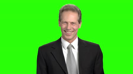 publicity : Cheerful man in suit shows ok gesture. Mature businessman smiling with teeth and showing ok gesture over green background.
