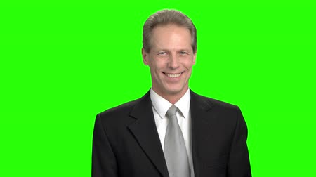 energized : Mature businessman pointing finger at you. Cheerful positive man gesturing you are cool, green background.