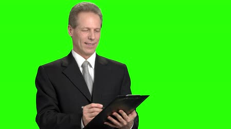 připomínka : Smiling mature man writing down on clipboard. Man doing remark on green hromakey background.