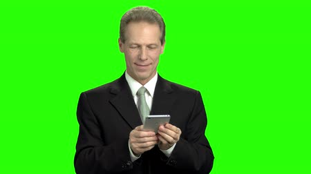 připomínka : Portrait of clerk messaging on smartphone. Mature man in black suit texting in chat online using both hands, green hroma background.