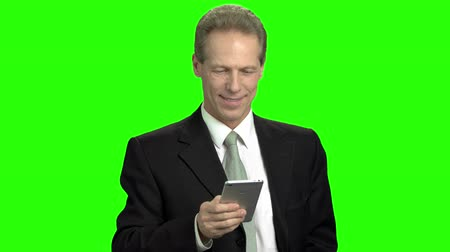tezgâhtar : Business man chatting on smartphone using one hand. Smiling mature man holding smartphone in his hand, green background. Stok Video