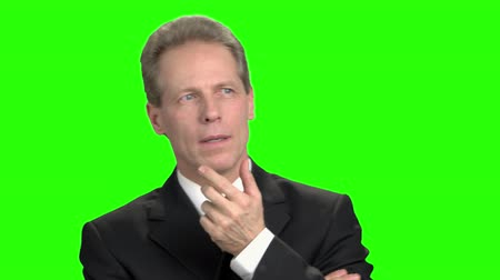 fancier : Pensive mature businessman in suit. Businessman think about something in green background. Stock Footage