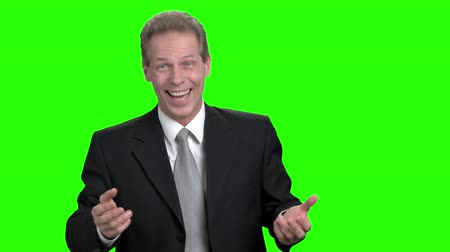 energized : Portrait of surprising and rejoicing businessman. Mature man in black suit wondering and starting to celebrate, green hroma background.