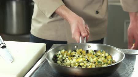 bakłażan : Hand of chef frying vegetables. Chopped eggplant, zucchini and pepper.