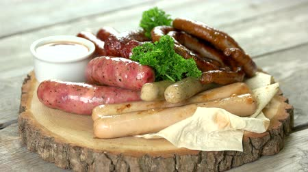 karkówka : Grilled sausages with sauce. Food on wooden board.
