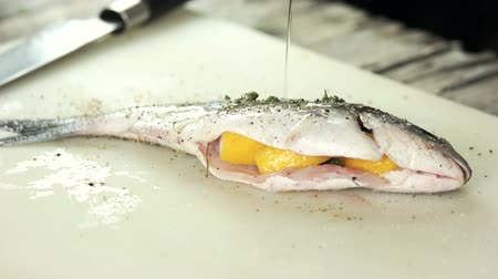 olive oil pour : Raw stuffed dorado fish. Food preparation, spices and oil.