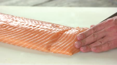 truta : Hands cutting fish. Raw salmon close up.