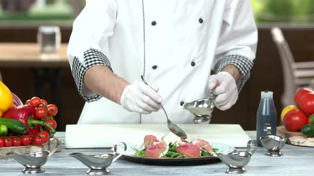 калория : Chef pouring sauce on salad. Food preparation, cooking table.