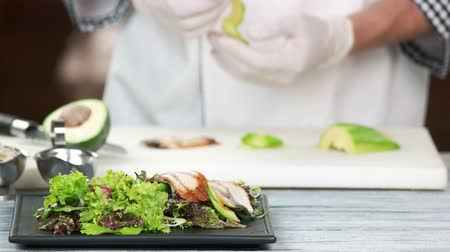 avokado : Chef preparing salad with eel. Lettuce, avocado and fish. Stok Video