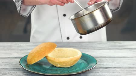 smetanový : Chef pouring soup from saucepan. Food in bread bowl.