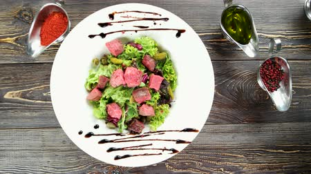 kapary : Beef salad top view. Food on brown wooden background.