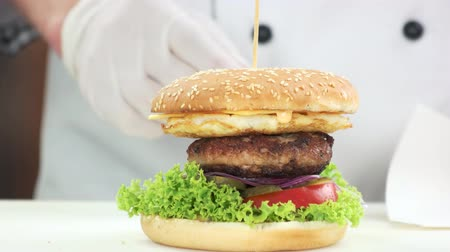 соленья : Hands of chef and burger. Beef burger close up. Стоковые видеозаписи