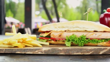 bagietka : Sandwich and fries close up. Fast food meal, wood board. Wideo