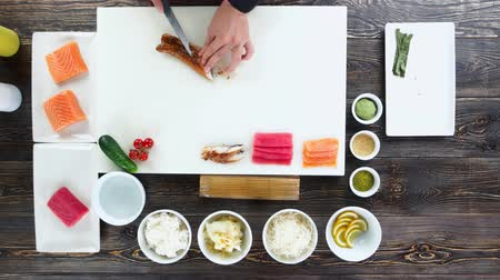 seafood recipe : Sushi ingredients top view. Hands cutting smoked eel. Stock Footage