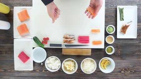 california rolls : Hands of sushi chef. Cutting board and food ingredients. Stock Footage