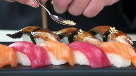 seafood recipe : Nigiri sushi close up. Smoked eel and sesame seeds.