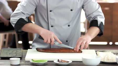 унаги : Sushi chef cutting smoked eel. Man preparing food, fish.