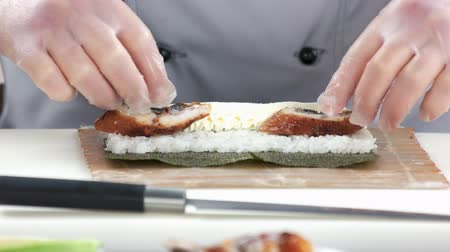 унаги : Hands making unagi sushi. Rice and smoked eel.