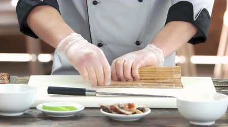 унаги : Hands making sushi, bamboo mat. Chef making japanese food.