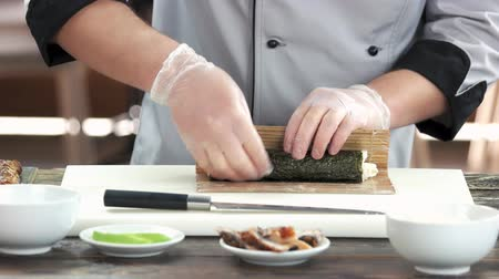 унаги : Sushi chef using bamboo mat. Japanese food preparation in restaurant.