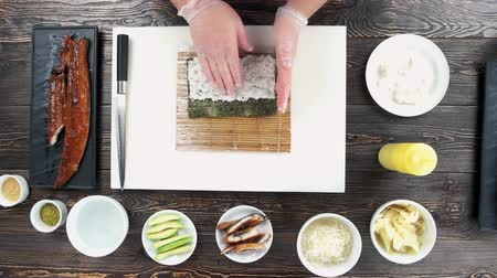 унаги : Sushi preparation, hands of chef. Cooking table, rice and nori. Стоковые видеозаписи