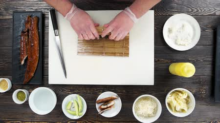 унаги : Sushi roll preparation top view. Chef making food, bamboo mat.