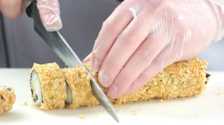 унаги : Hands cutting sushi close up. Unagi maki rolls, crispy breading. Стоковые видеозаписи