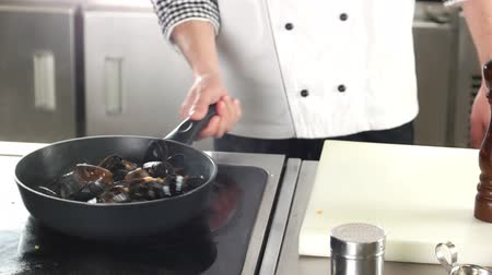 midye : Chef cooking seafood. Mussels with vegetables.