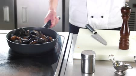 shellfish dishes : Chef cooking mussels. Seafood in frying pan. Stock Footage