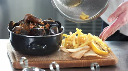 shellfish recipe : Mussels and fries. Food on a wooden board.