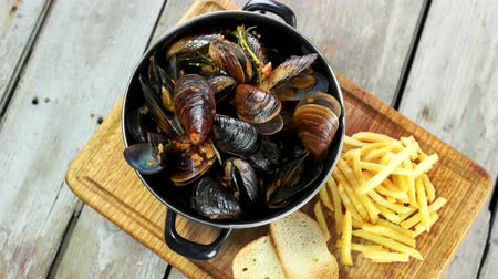 shellfish dishes : Mussels with toasts and fries. Restaurant meal top view. Stock Footage