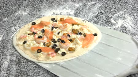 pílula : Uncooked pizza on a shovel. Shrimps, salmon and olives.